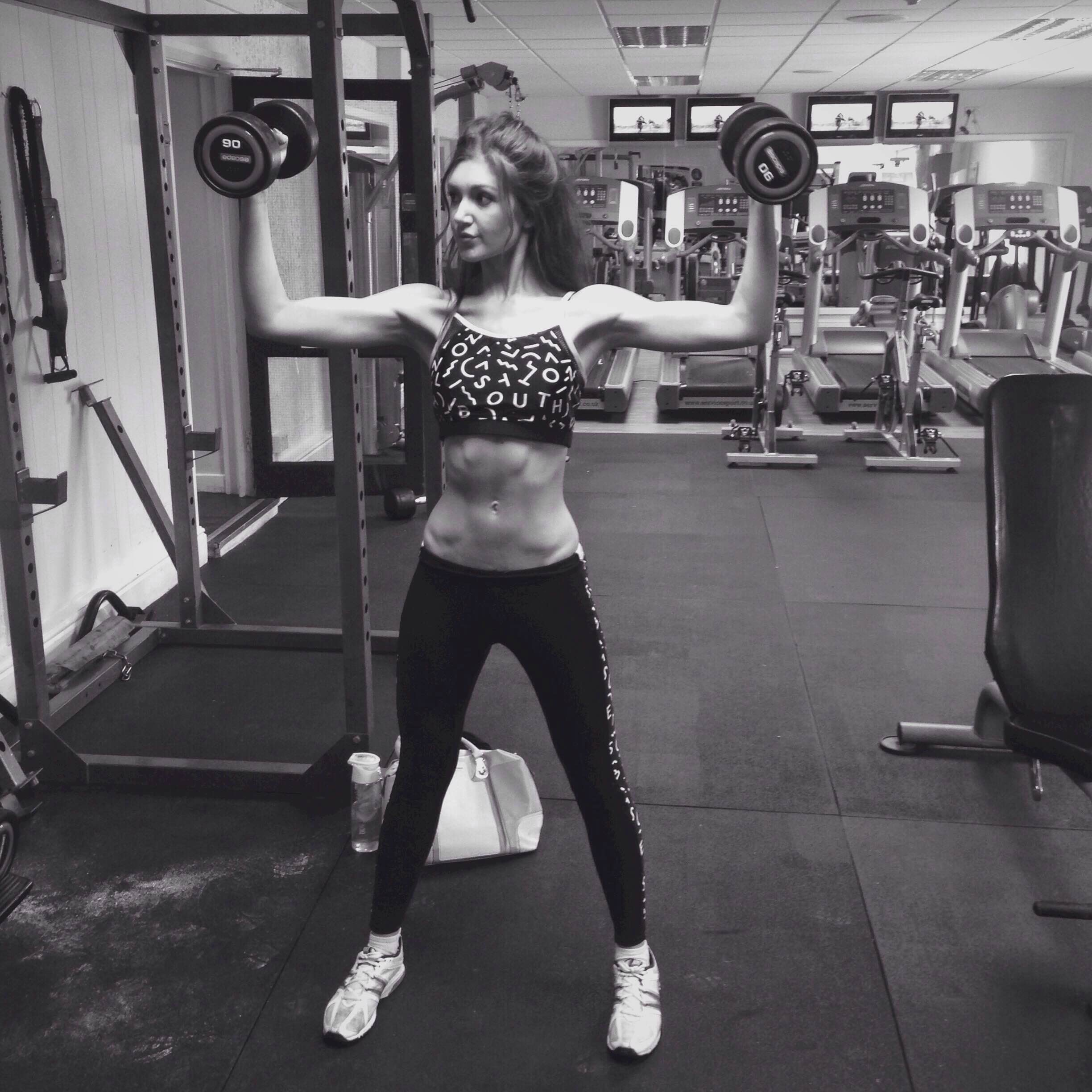 girl in gym lifting weights